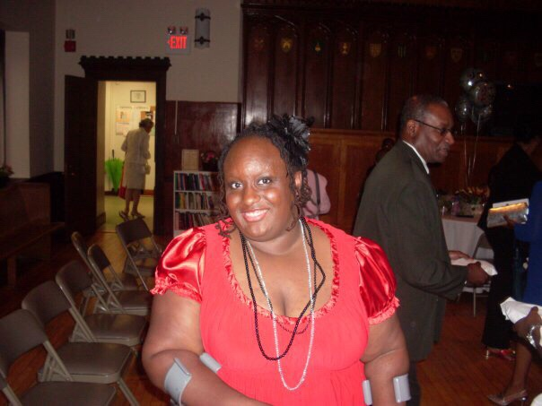 Imani in a red dress standing in a church.